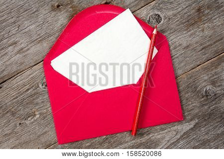 Blank paper red envelope and pencil on wooden background