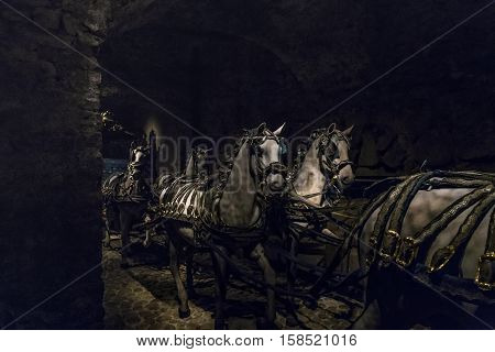 STOCKHOLM, SWEDEN - JUNE 28, 2016: This is layout of team horses of royal carriage in the hall of royal carriages of the Armory (Livrustkammaren) at the Royal Palace.