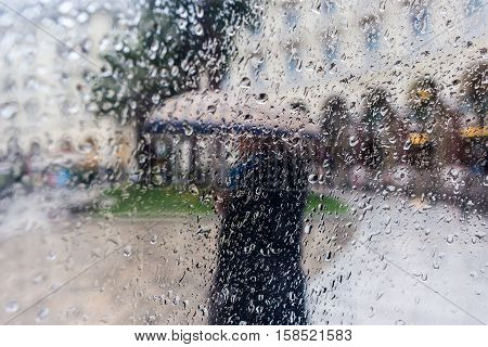 Raindrops On A Window Pane. Blur People In The Rain.