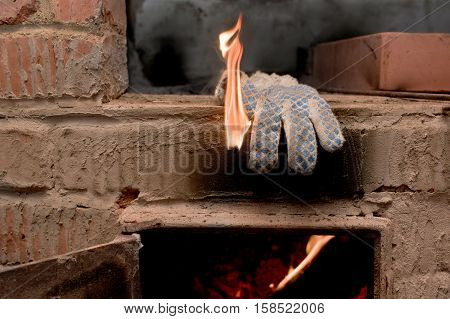 Open door of a fireplace and protective glove in fire concept of danger and negligence. Closeup indoor shot