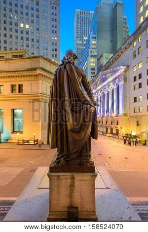 NEW YORK CITY - OCTOBER 23, 2016: The George Washington statue at Federal Hall stands before the New York Stock Exchange on Wall Street.