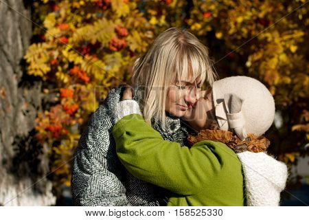 Mother and daughter outdoors in autumn on a background of rowan