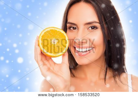 Beautiful Woman Holding Half Of Orange Over Background With Snowflakes
