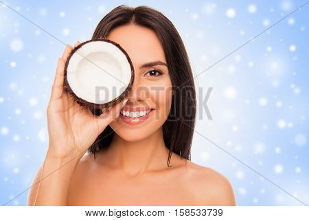 Cheerful Pretty Young Woman Holdind Coconut Covered With Snow