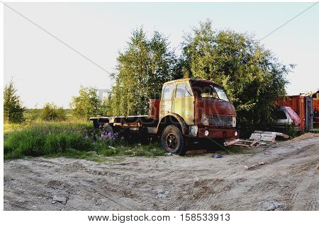 Orange old lorry stay at the tree. Summer