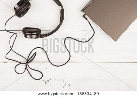 Audio Book Concept With Black Book And Headphones On White Woode