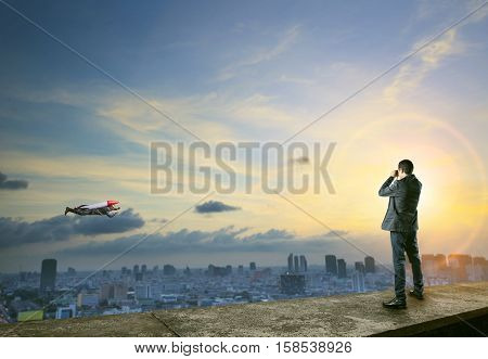 business man binocular to man with rocket on back flying over city scape comedy concept in business competition theme