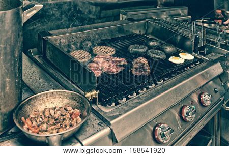 Real kitchen of a bar and grill restaurant in operation, toned image