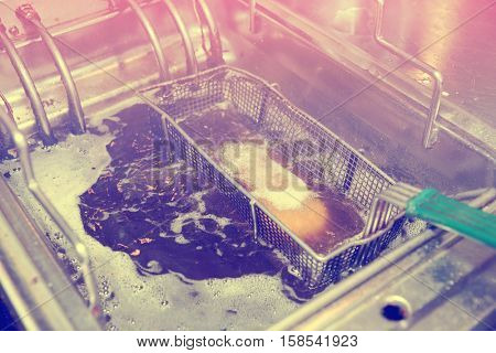 Deep fryer with boiling oil on restaurant kitchen, toned image