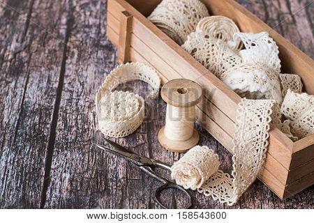 Wooden box with lace ribbons, scissors and a sewing thread reel on the old wooden table.