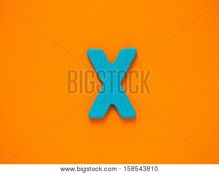 Capital letter X. Blue letter X from wood on orange background.