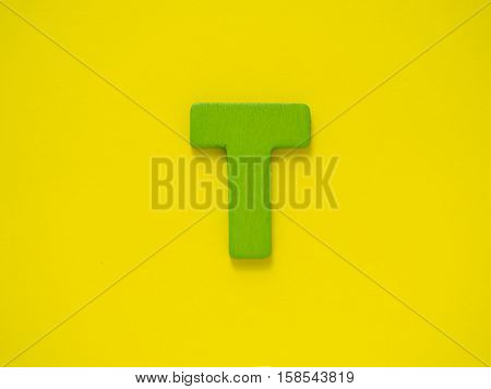 Capital letter T. Green letter T from wood on yellow background.