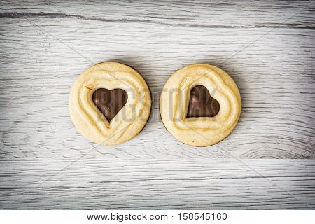 Two jam biscuits in the shape of heart on the wooden background. Food theme. Symbolic sweets. Valentine's Day.