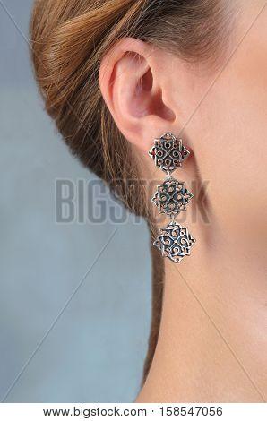 Female ear in jewelry earrings close up