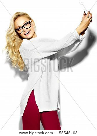 beautiful happy sweet cute smiling blonde woman model in casual hipster warm white sweater clothes in glasses taking selfie