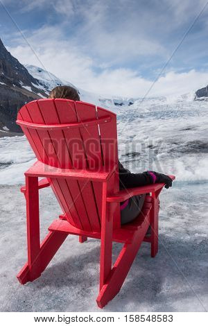 Relaxing on Athabasca Glacier in a red adirondack chair