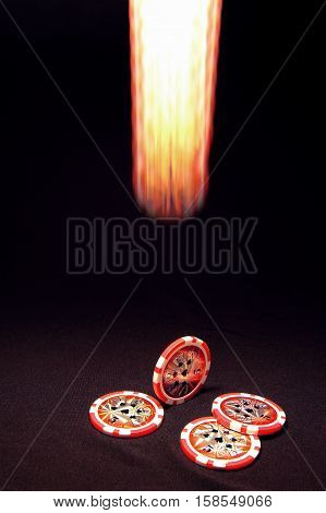 Luminous falling poker chip on black background and heap of red poker chips