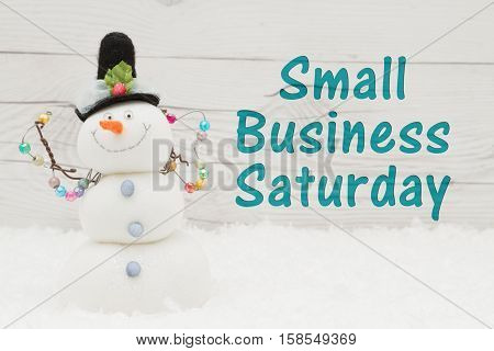 Small Business Saturday message Some snow and a snowman on weathered wood with text Small Business Saturday
