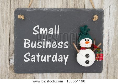 Old fashion Christmas store message A retro chalkboard with a snowman hanging on weathered wood background with text Small Business Saturday