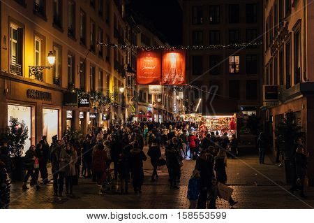 STRASBOURG FRANCE - NOV 28 2015: People walking under immense crystal chandeliers from Baccarat on the rue des Hallebardes in Strasbourg France with immense light illuminations Alsace