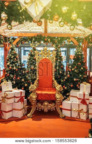 Majestic and luxurious red and gold chair Santa Claus throne surrounded by multiple presents white boxes with red ribbon gift boxes vintage modern