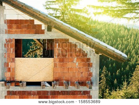 Unfinished vacancy house in the mountains surrounded by beautiful green nature on a sunny day