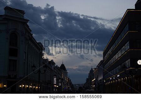dark street buildings silhouette and drammatic cloudy sky