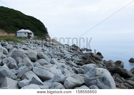 Rocky shore. Tent on the beach. The girl catches a fish. The machine on the beach. Relax on the beach. Japanese Sea.