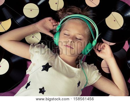 Beautiful girl lying next to vinyl records and listening to music on headphones. Top view.