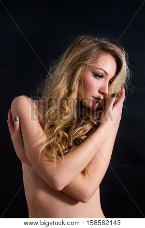 Sensual topless beautiful blond haired girl isolated on black background, emotive fashion portrait, arms crossed, shy