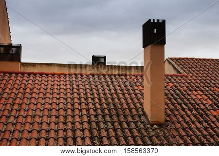 Roof with reddish tiles and chimneys with metallic cover