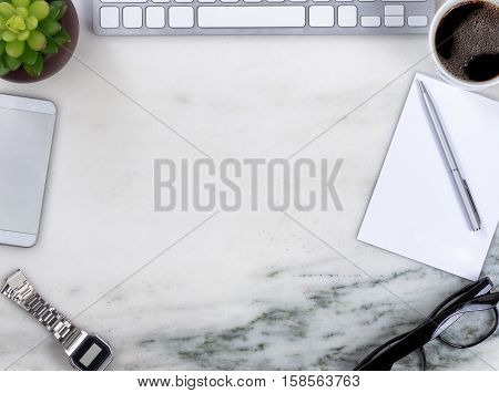 Overhead view of marble office desktop with computer keyboard cell phone pen paper reading glasses coffee watch and plant forming circle border.