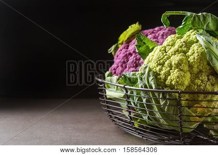 Rainbow Of Organic Cauliflower In A Metal Basket With A Dark Clo