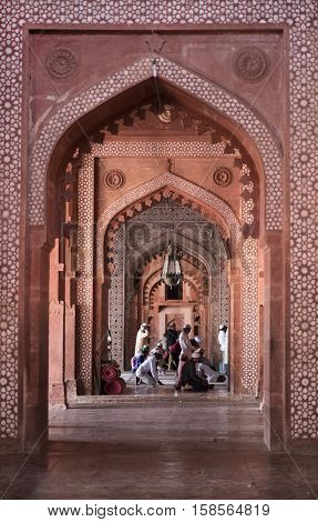 Agra, India - October 12: Muslims praying inside the red sandstone doorway and hall of the fort Jama Masjid Friday Mosque on October 12, 2016 in Fatehpur Sikri, Agra, India. Jama Masjid is World Heritage Site and one of the largest mosques in India.