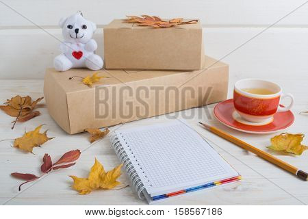 two craft paper box notebook pencil cup of tea white bear with a heart decorate autumn leaves. Romantic bisness concept.