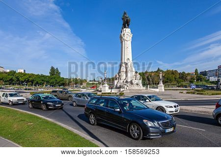 Lisbon, Portugal - October 19, 2016: Marques de Pombal Roundabout. An UBER vehicle transports a passenger, followed by a TAXI.