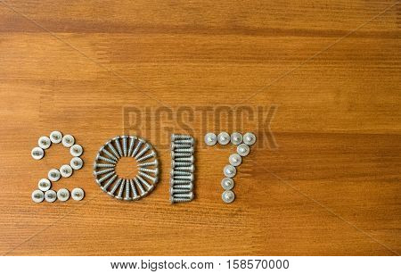 Happy new year 2017 composition with screws on wooden background. New year. New year background. New year 2017. Concept constructions.
