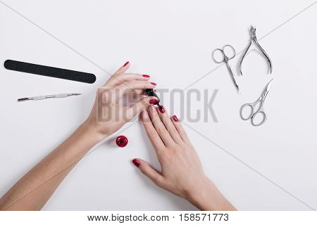 Top View Of Female Hands Painted Nails With Red Lacquer