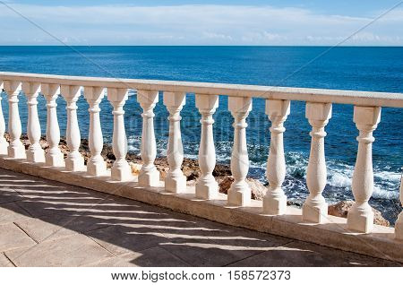 Sea and fence with white balusters and blue sky.