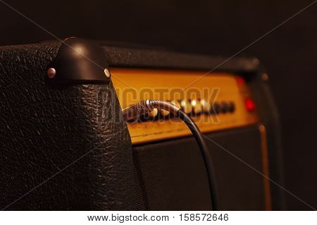 Combo amplifier for electric guitar with inserted input jack on the black background. Shallow depth of field low key close up.