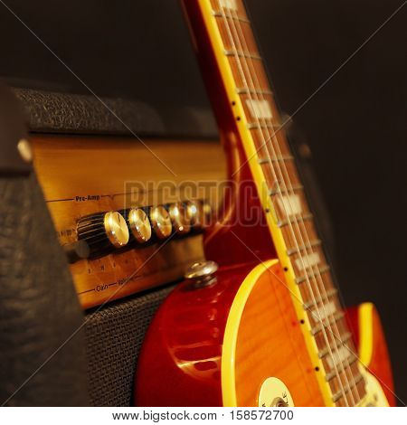 Electric guitar with amplifier on the black background. Shallow depth of field low key close up.