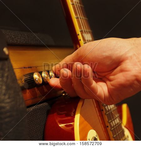 Hand adjusts combo amplifier for guitar with electric guitar on the black background. Shallow depth of field low key close up.