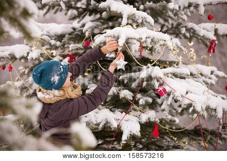 Portrait of young woman decorating Christmas tree outdoors. Girl walking in the winter park. Christmas and winter concept.