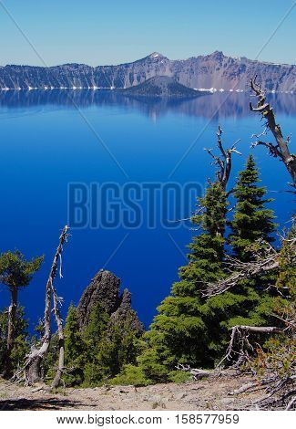 Wizard Island in the deep blue waters of Crater Lake seen from the opposite bank on a sunny summer afternoon in the Cascade Mountains of Oregon.