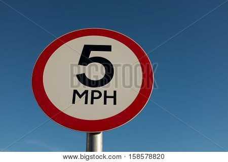 A circular road traffic sign with ' 5 MPH' on a white background with a red border against a blue sky.