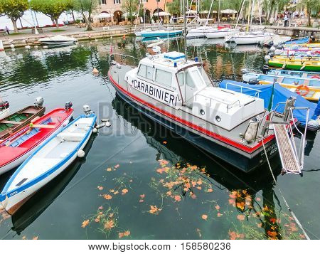 Torri Del Benaco, Italy - September 20, 2014: Fishing boats and Carabinieri boat in the small harbor of Torri del Benaco, Garda Lake, Italy on September 20, 2014