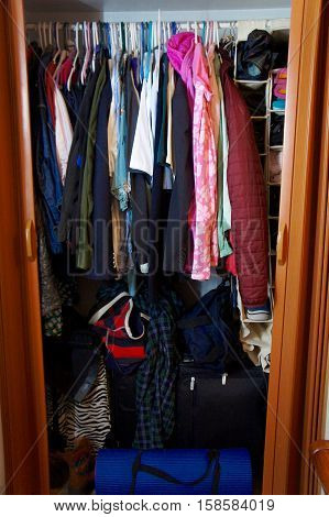 Over Crowded Small Clothes Closet with Luggage, Clothes and Shoes
