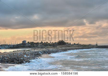 High tide swell crashing against marina rocks at dawn.