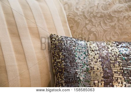 a variety of luxury decor cushions in beige and champagne tones with a little bling