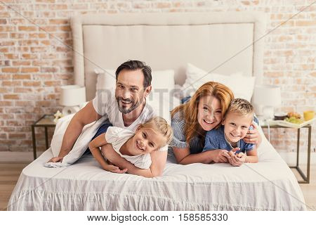 Family laughs together. Cheerful middle-aged parents embracing little children, spending time at home while lying on bed
